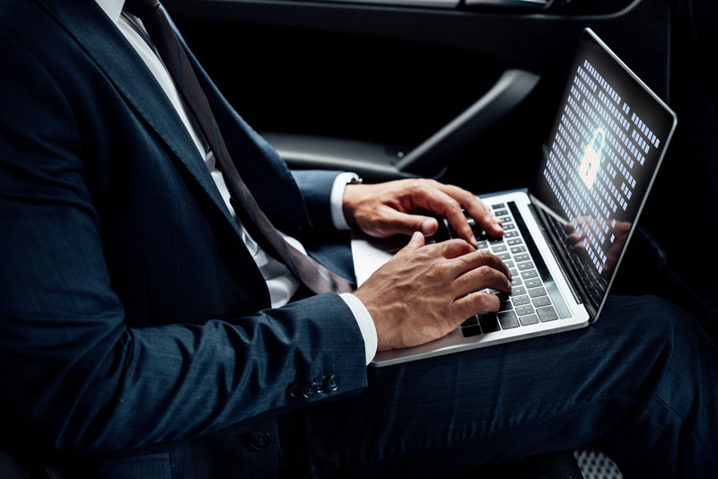 Man with security pulled up on his laptop