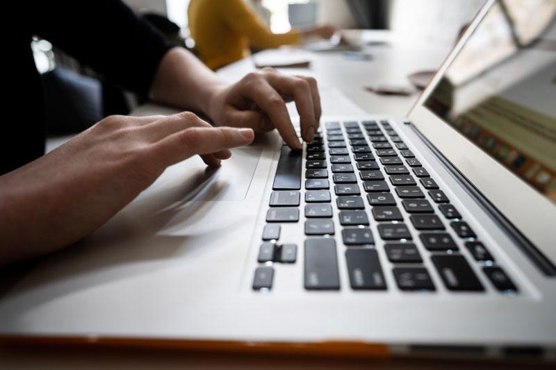 A man typing on a laptop keyboard
